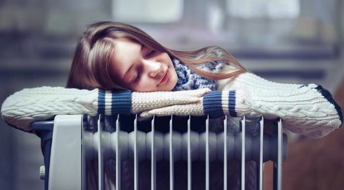 Girl feeling the warmth of a radiator