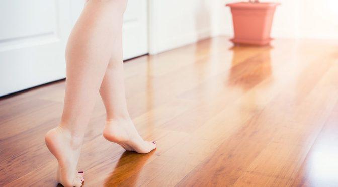 Bear feet walking on a warm heated laminate floor